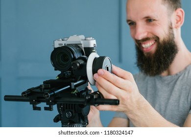 cameraman lifestyle and video shooting hobby. man creating content for broadcast or blog using camera on holder and tripod. modern equipment and tools concept.