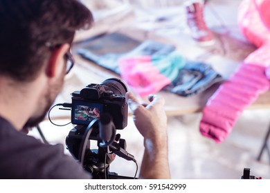 Cameraman is looking at the camera display on the set in studio with blurred colorful background. Moment from shooting with preparation of the shot. Color toned image.