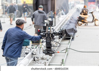 A cameraman looking to the display of big professional video camera moving on a rails on a movie set.