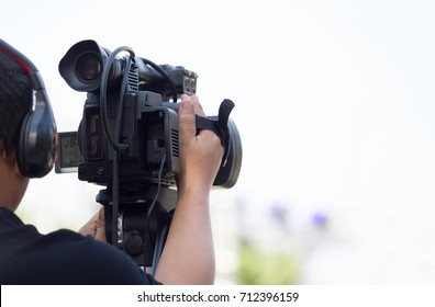 cameraman on duty with professional camcorder with blur background