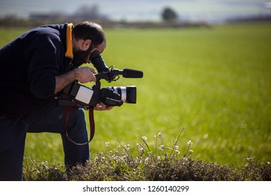 a cameraman with a professional camcorder in a green idyllic field
