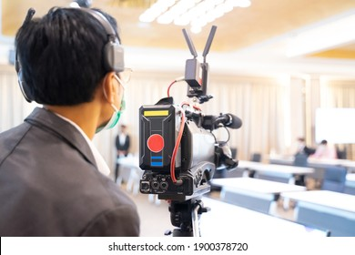 The cameraman setting up the camera for the upcoming conference
