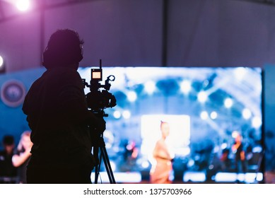 Cameraman silhouette on a live studio news stage.Professional cameraman with headphones with camcorder in television news broadcast.