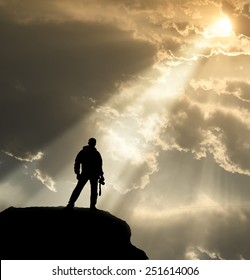 cameraman silhouette standing on cliff with god light and sky and cloud background