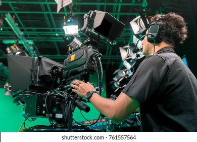 Cameraman taking a broadcast camera in broadcast television virtual green screen studio room.