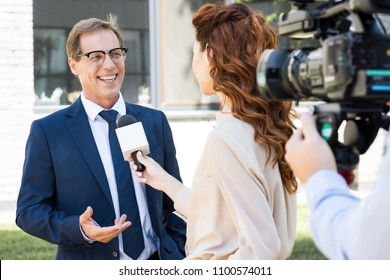 cameraman with video camera and anchorwoman interviewing successful businessman