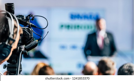 Cameraman wearing headphones and recording male speaker standing on the stage at press conference media event. Live streaming concept.