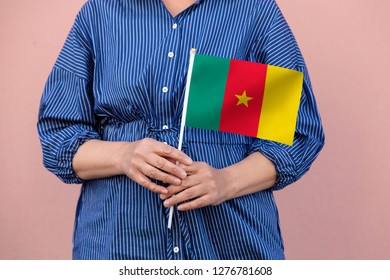 Cameroon flag. Close up of hands holding national flag of Cameroon
