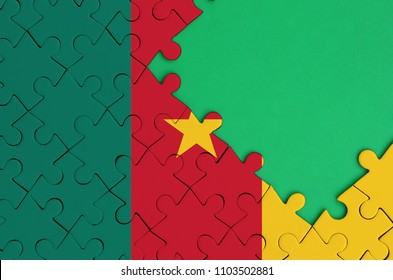 Cameroon flag  is depicted on a completed jigsaw puzzle with free green copy space on the right side