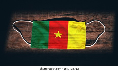 Cameroon National Flag at medical, surgical, protection mask on black wooden background. Coronavirus Covid–19, Prevent infection, illness or flu concept photo. State of Emergency, Lockdown
