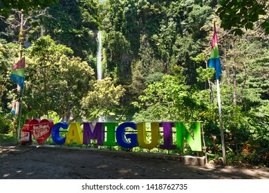 Camiguin Island, 04 17 2019: Colorful sign of Camiguin in front of Katibawasan waterfall