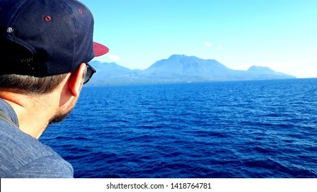 Camiguin Island, Philippines - 04 19 2019: Young man viewing the volcano of Camiguin Island during the ferry ride