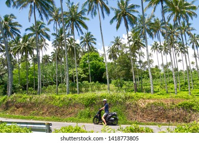 Camiguin Island, Philippines - 04 20 2019: Young man driving a motorcycle / motorbike around the island