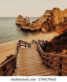 Camilo Beach at Algarve, Portugal with turquoise sea in background. Wooden footbridge to beach Praia do Camilo, Portugal.