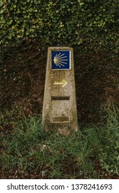 Camino de Santiago post made of stone, with yellow arrow and sign.