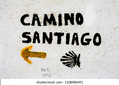 Camino de Santiago sign post with yellow arrow and black shell symbol at a white wall