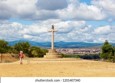 Camino de Santiago (Spain) - The Santo Toribio stone cross and a pilgrim walking along the way of St.James, near Astorga