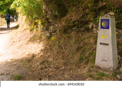 Camino de santiago waymark and walking pilgrims in Sarria. Road sign made in stone used for pilgrims to walk in the correct direction to Santiago de Compostela