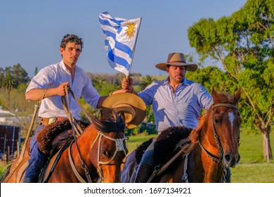 CAMINOS, CANELONES, URUGUAY, OCT 7, 2018: Gauchos riding horses and waving the Uruguayan flag in Uruguay, South America, also been seen in Argentina, Brazil and Chile