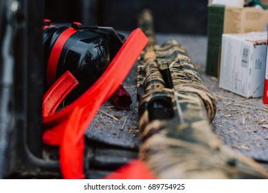 Camo rifle sitting in the back of a truck with other gun accessories for skeet shooting.