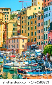 Camogli, Genoa, Italy - July 3, 2019:  Colorful buildings and fishing boats in the port of Camogli on sunny summer day, Liguria