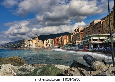 Camogli, Italy is a resort seaport town on the Italian riviera.  The rocky beach is a popular tourist vacation area.  At the far end is the famous Basilica Di Santa Maria