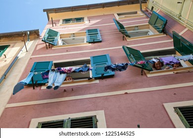 CAMOGLI, ITALY - SEPTEMBER 21, 2009: Unidentified people protrude from the window between the laundry hanging