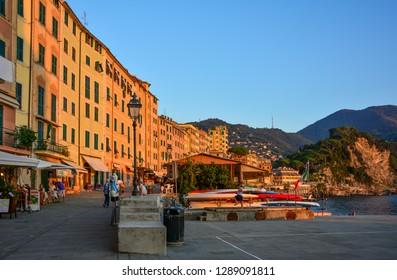 Camogli / Italy — September 28, 2016: view of the sea promenade in Camogli, a small fishing village on the Italian riviera, at sunset. Located near Portofino, Camogli is a popular tourist destination