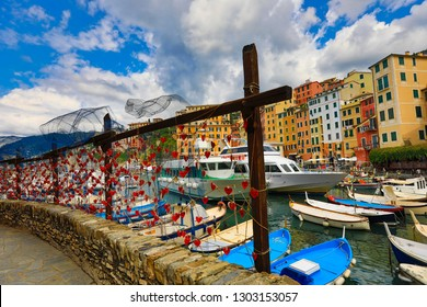 CAMOGLI, ITALY/EUROPE - SEPTEMBER 3, 2018:  Love notes are tied to the fence along the pier in the resort town of Camogli, Italy.  The harbor is full of boats and yachts.