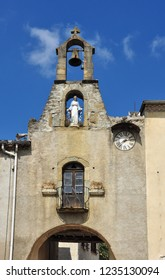 CAMON, ARIEGE, FRANCE - September 10, 2018. Statue and bell over the Porte de l'Horloge or Clock Gate in the fortified village of Camon, Ariege, Occitanie, France