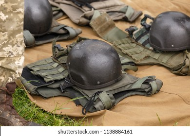 Camouflage combat flak jackets and helmets lined up on the ground