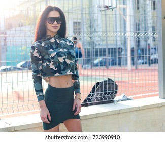 127f222040aea Camouflage. Fashion on the street. Beautiful brunette girl in short khaki  skirt and super