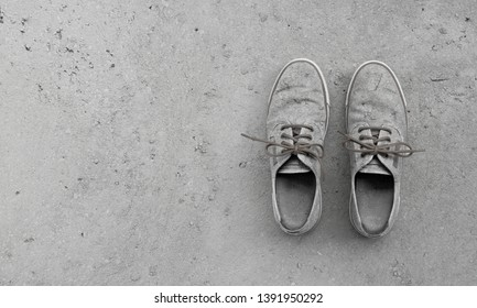 camouflage pair of old grungy shoes on concrete background with copy space