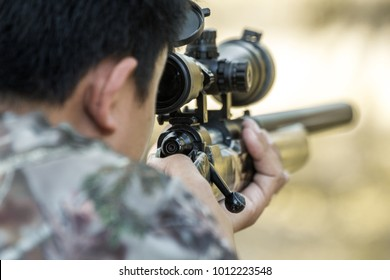Camouflage sniper shooting rifle by looking through a scope hunting.