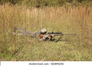 Camouflaged hunter in grassy area with sniper rifle looking through scope at target.