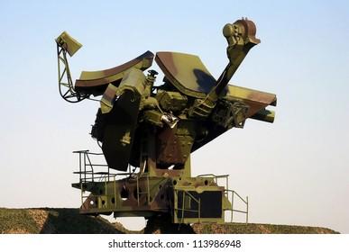 Camouflaged mobile military radar opposite blue sky