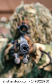 Camouflaged sniper keeps victim at gunpoint. Soldier dressed in ghillie camouflage on nature