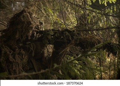 Camouflaged sniper keeps victim at gunpoint. Soldier dressed in ghillie camouflage on nature.