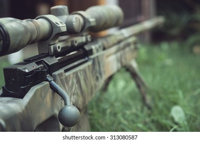 Camouflaged sniper rifle with spotting scope and equipment. Photo edited into warfare look and dark atmosphere. Selective focus.