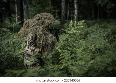 Camouflaged soldier with assault rifle during patrol in forest
