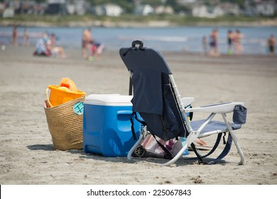Camp chair, picnic box and a picknic basket on the beach, blurred people in backgraund