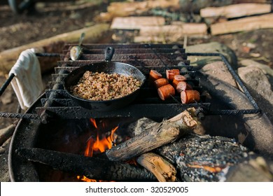 Camp cooking, grains and sausage cooking over the fire