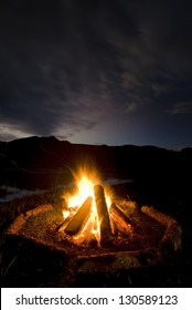 Camp fire beside lake and mountains.