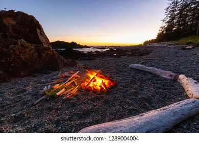 Camp fire on the beach during a vibrant summer sunset. Taken in Northern Vancouver Island Ocean Coast, BC, Canada.