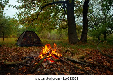 Camp fire and tourist tent in the background