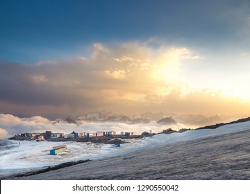 Camp in highland on snow mountain slope over clouds. Highland settlement on Elbrus mountain. Extreme hotel made from containers over mountain ridge. Beautiful high mountain landscape on sunset.
