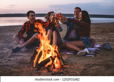 Camp on the beach. Group of young friends having picnic with bonfire. They drink beer