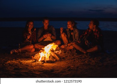 Camp on the beach. Group of young friends having picnic with bonfire. They have fun