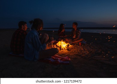 Camp on the beach. Group of young couples having picnic with bonfire