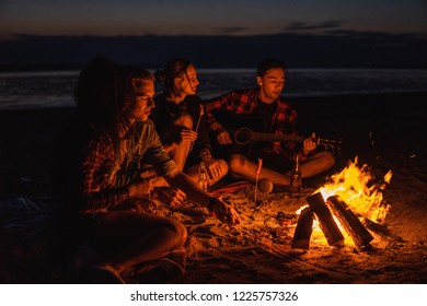 Camp on the beach. Group of young friends having picnic with bonfire. Man is playing guitar